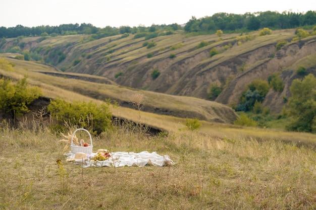Stijlvolle zomerpicknick op een witte deken. op een schilderachtige plek de natuur van de heuvels.