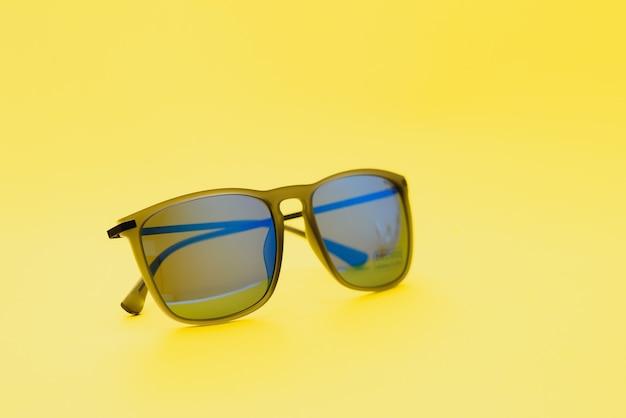 Stijlvolle zonnebril op een gele achtergrond hoge kwaliteit foto zonnebril.