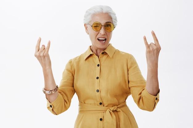 Stijlvolle, zorgeloze senior vrouw in zonnebril met rock-n-roll-gebaar en glimlachen, plezier maken