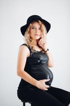 Stijlvolle zwangere vrouw in zwarte hoed en sprankelende top omarmen haar buik.