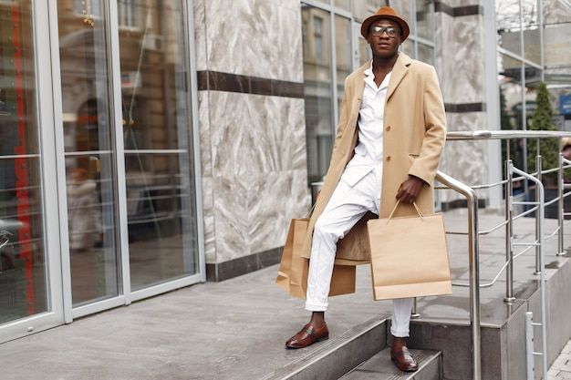Stijlvolle zwarte man in een stad met boodschappentassen