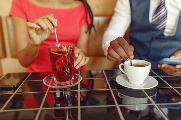 Stijlvolle zwarte paar zitten in een café en een kopje koffie drinken