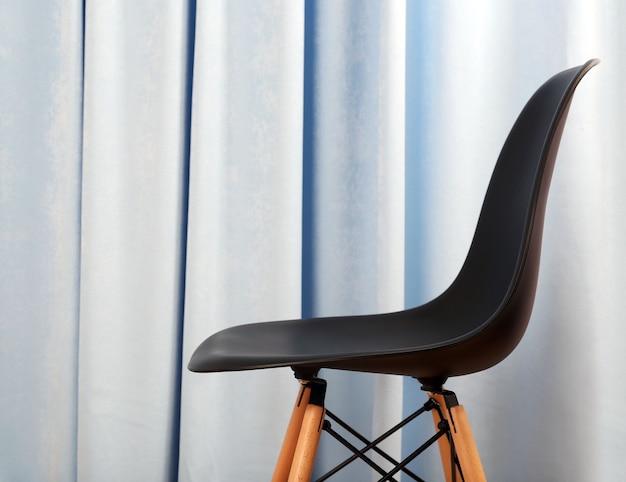 Stijlvolle zwarte stoel op blauwe gordijnen oppervlak