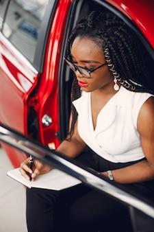 Stijlvolle zwarte vrouw in een autosalon
