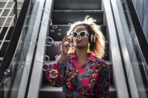 Stijlvolle zwarte vrouw in hoofdtelefoon bellen blazen op bewegende trap