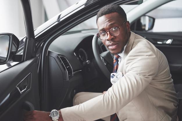 Stijlvolle zwarte zakenman achter het stuur van een nieuwe luxeauto. rijke afro-amerikaanse man.