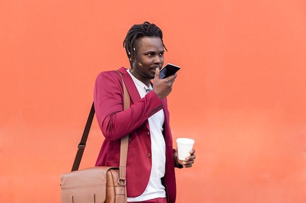 Stijlvolle zwarte zakenman gekleed in pak met aktetas en koffie neemt een spraakbericht op zijn smartphone op voor rode achtergrond, kopieer ruimte voor tekst, concept van technologie en communicatie