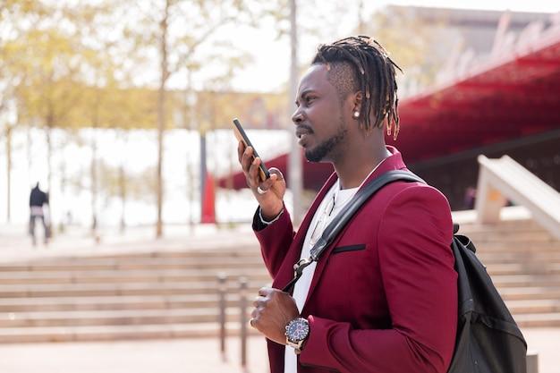 Stijlvolle zwarte zakenman neemt een spraakbericht op zijn smartphone op terwijl hij door de stad loopt, kopieert ruimte voor tekst, concept van technologie en communicatie