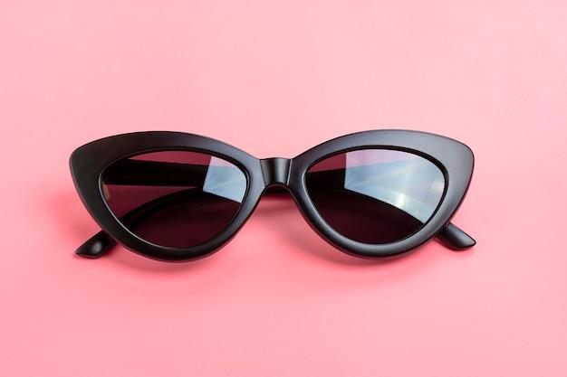 Stijlvolle zwarte zonnebril geïsoleerd op trendy roze