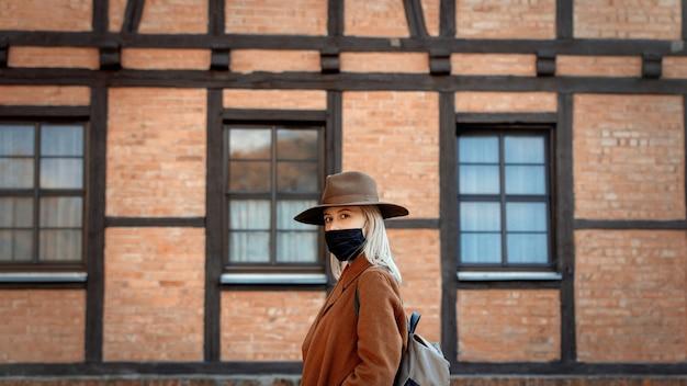 Stijlvrouw in hoed en gezichtsmasker met houten huis