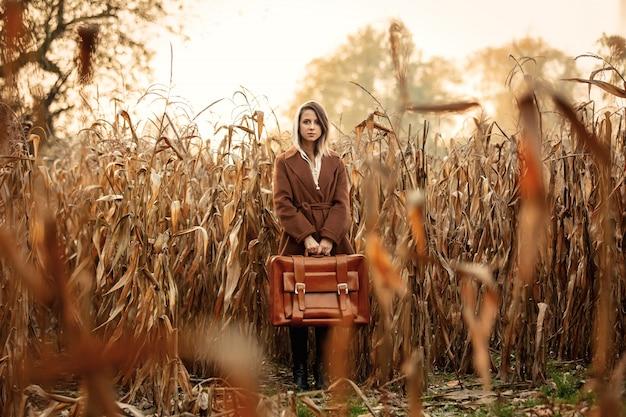 Stijlvrouw in laag met koffer op graangebied in het seizoen van de de herfsttijd