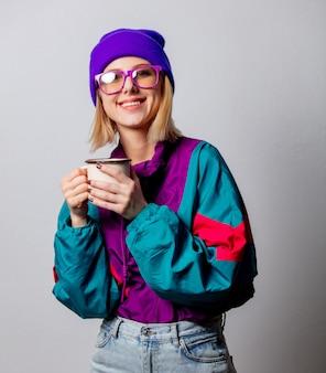 Stijlvrouw in punkkleren uit de jaren 90 met koffiekopje