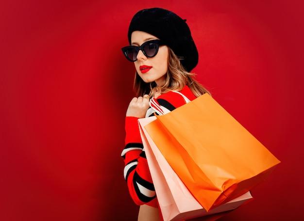 Stijlvrouw in zonnebril met het winkelen zakken op rode muur