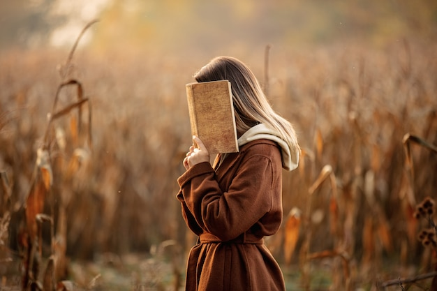 Stijlvrouw met boek op graangebied in het seizoen van de de herfsttijd