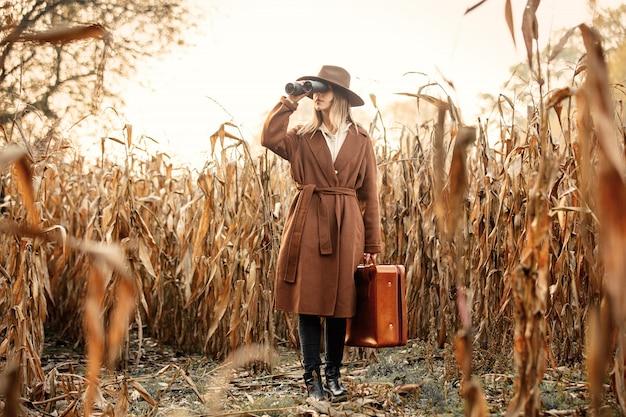 Stijlvrouw met reiskoffer en verrekijker op graangebied in het seizoen van de de herfsttijd