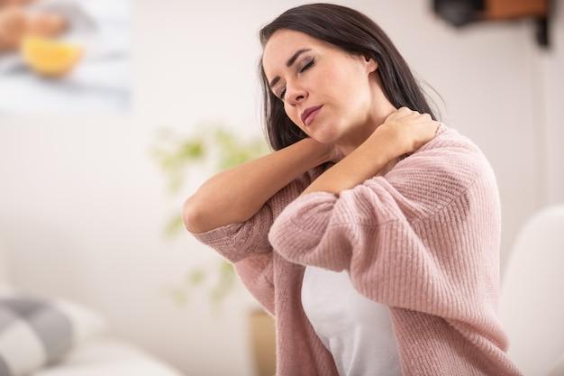 Stijve nek van een vrouw als ze thuis opvalt vanaf een bank.