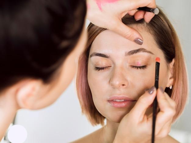 Stilist die oogschaduw op model toepast