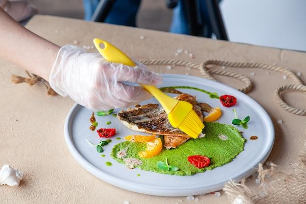 Stilist met kwastjes die gebakken zeebaarsfilet voorbereiden met groene erwtenpuree, tomaat, sinaasappelplakken.