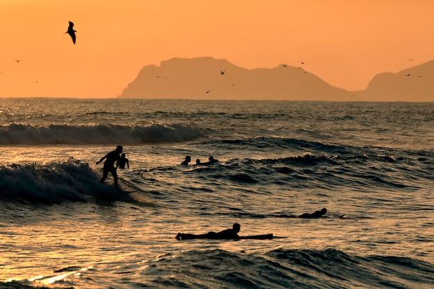 Stille oceaan. silhouetten van de surfers en de berg bij zonsondergangtijd. lima, peru. zuid-amerika