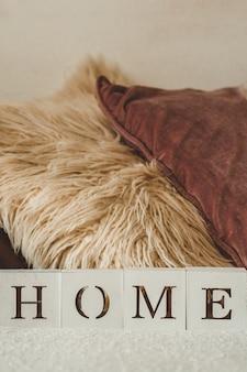 Stilleven details in interieur van woonkamer en het opschrift home. veel decoratieve gezellige kussens. rust uit. gezellig herfst- of winterconcept, breigoed. thuis concept