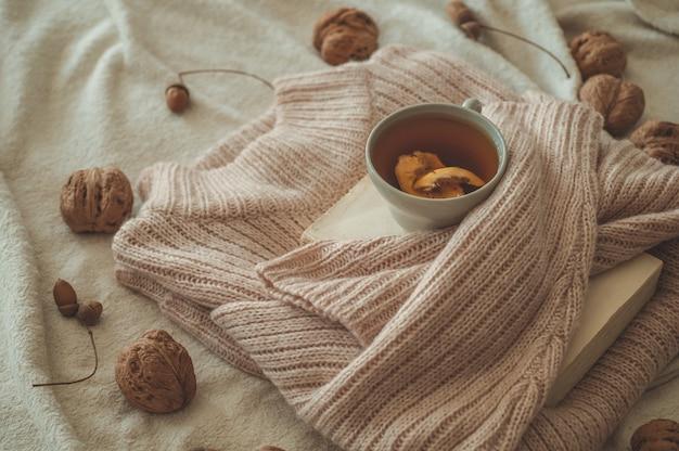 Stilleven details in interieur van woonkamer. truien en kopje thee met kegel, nootjes en herfstdecor in de boeken. lees, rust. gezellig herfst- of winterconcept.