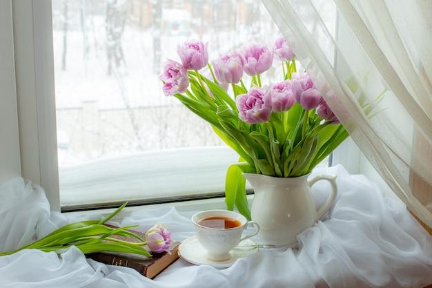 Stilleven een boeket van lila tulpen in een vaas een mok thee een oud boek op het raam