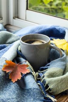 Stilleven een kopje koffie en herfstbladeren met plaid