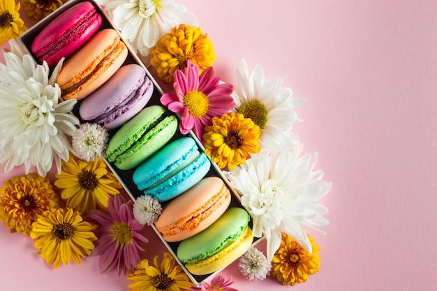 Stilleven en voedselfoto van cake macarons in een geschenkdoos met bloemen, een kopje thee