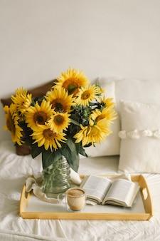 Stilleven in huisbinnenland van woonkamer. zonnebloemen, koffie en open boek. lees, rust