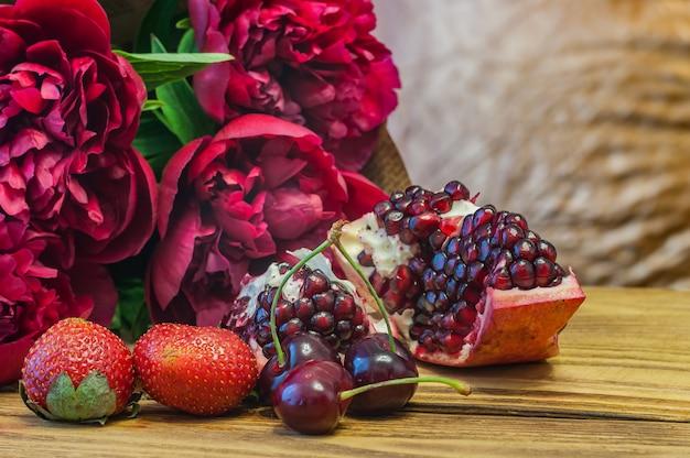 Stilleven in rode tonen. pioenrozen, granaatappel, kers en aardbei.
