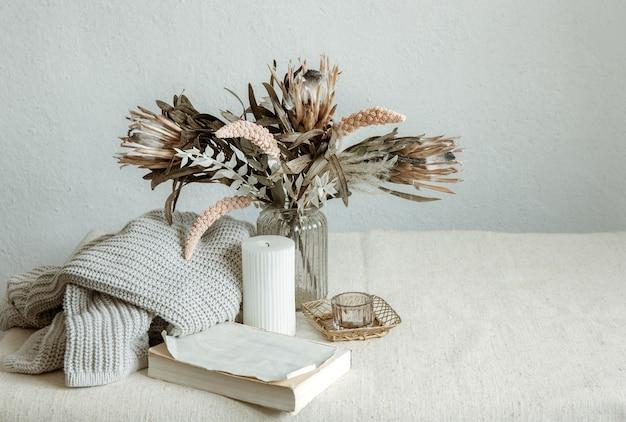 Stilleven in scandinavische stijl met een boeket bloemen, een gebreid element en decoratieve details