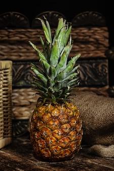 Stilleven met ananas op houten rustieke lijst.