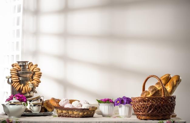 Stilleven met broodjes, bagels, marshmallows en een samovar op tafel