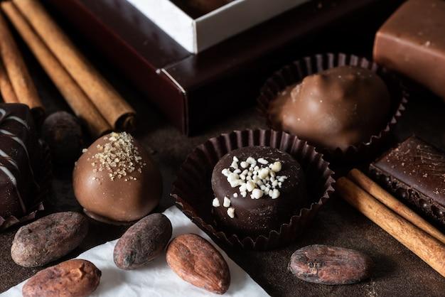 Stilleven met chocoladesuikergoed, kaneel en cacaobonen op een donkere achtergrond.