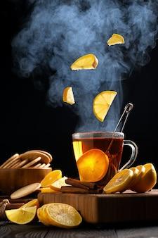 Stilleven met citroenen die in een mok hete thee vliegen, stoom stijgt boven de mok