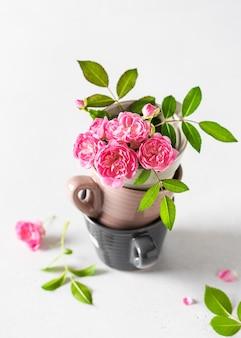 Stilleven met delicate miniroze roosjes en pastelkleurige espressokapjes