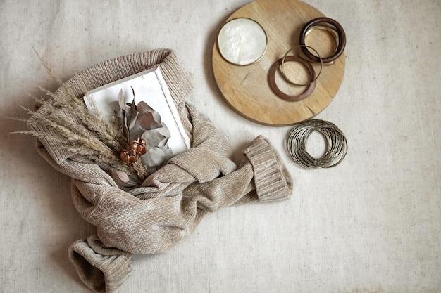Stilleven met details. boeket gedroogde bloemen op een warme trui en vrouwen armbanden bovenaanzicht, herfst concept.