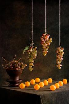 Stilleven met druiven en oranje ballen
