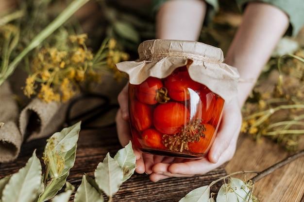 Stilleven met een blikje tomaten in blik tussen kruiden en kruiden.
