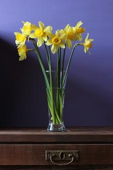Stilleven met een boeket gele gele narcissen in een glasvaas op een lijst met een lade.