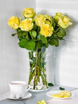 Stilleven met een boeket gele rozen en een kopje thee