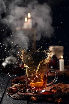 Stilleven met een glas thee met citroen en een scheutje water en stoom uit het glas
