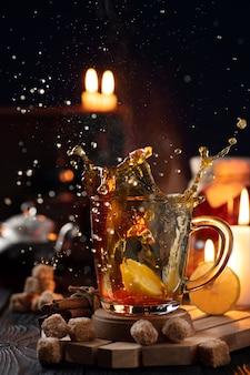 Stilleven met een glas thee met citroen en een scheutje water uit het glas.