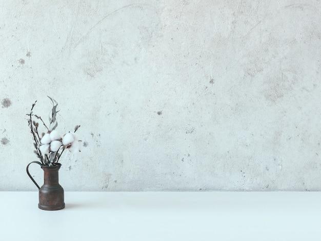 Stilleven met een klein koperen kannetje met een boeket droogbloemen op een witte tafel met een betonnen wand. katoenen bloemen, eucalyptus, wilg.