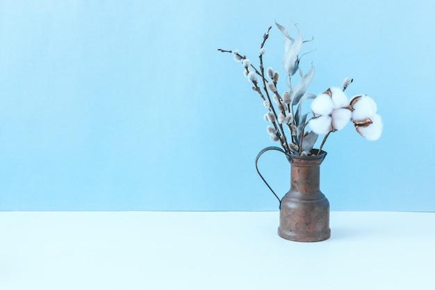 Stilleven met een klein koperen kannetje met een boeket droogbloemen op een witte tafel met een blauwe muur. katoenen bloemen, eucalyptus, wilg.