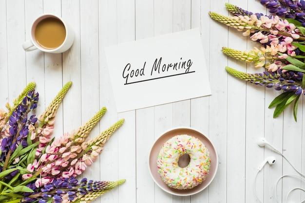 Stilleven met een kopje koffie en lupine bloemen donut op een licht houten tafel.