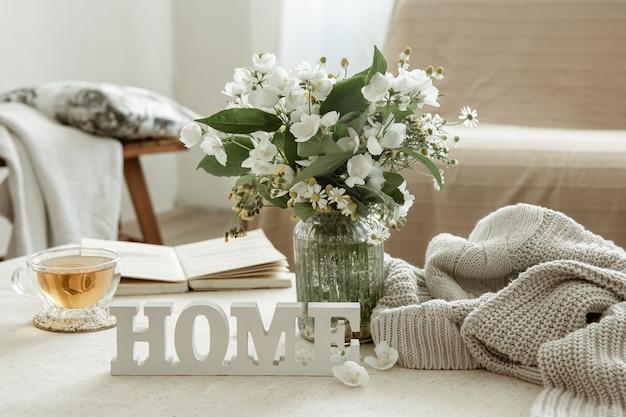 Stilleven met een kopje kruidenthee, een boeket bloemen, een boek en een houten decoratief woord huis.