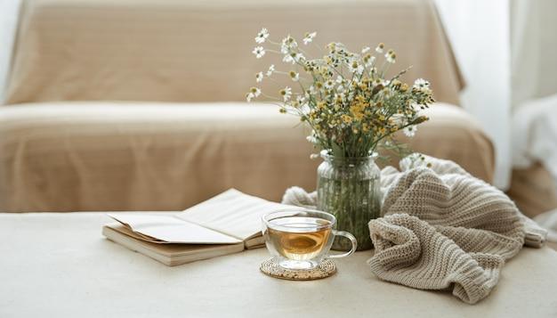 Stilleven met een kopje kruidenthee, een boeket wilde bloemen, een boek en een gebreid element.