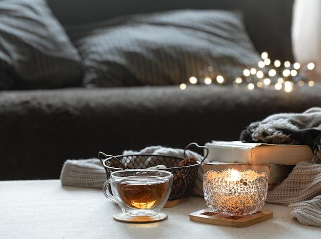 Stilleven met een kopje thee, een theepot, boeken en een brandende kaars in een kandelaar met bokeh.