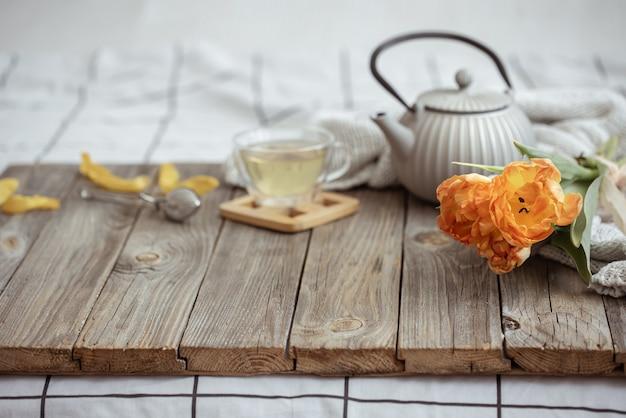 Stilleven met een kopje thee, een theepot en een bosje tulpen